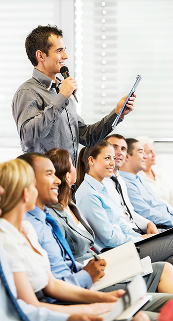 A photo of a group of people in a presentation skills workshop